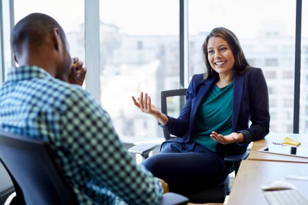 schöne geschäftsfrau mit männlicher kollege in kreativbüro zu diskutieren. junge führungskräfte sitzen auf stühlen gegen fenster. sie sind smart casual tragen. - gestikulieren stock-fotos und bilder
