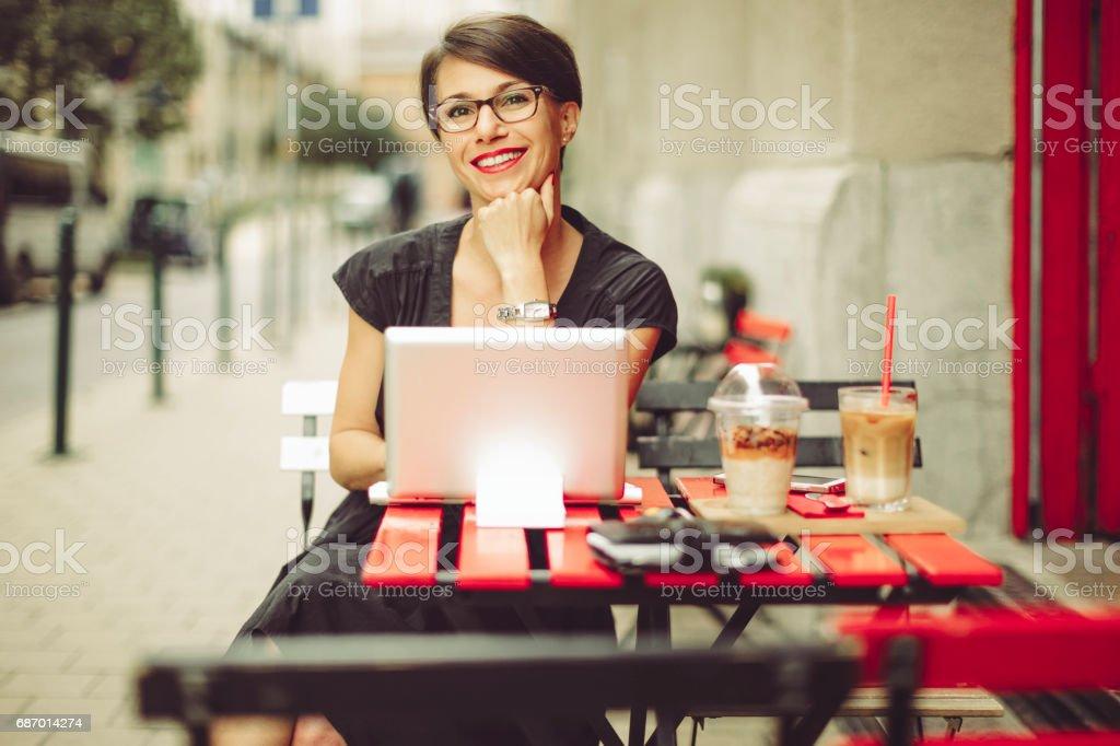 Schöne Geschäftsfrau mit Frühstück in einem coffee shop Lizenzfreies stock-foto