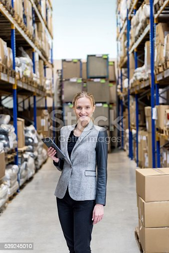 915900234istockphoto Beautiful businesswoman holding tablet in warehouse 539245010