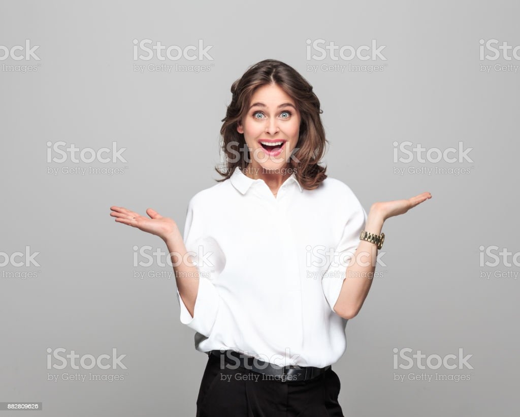 Beautiful businesswoman looking surprised Portrait of beautiful businesswoman with surprised facial expression against grey background. 25-29 Years Stock Photo