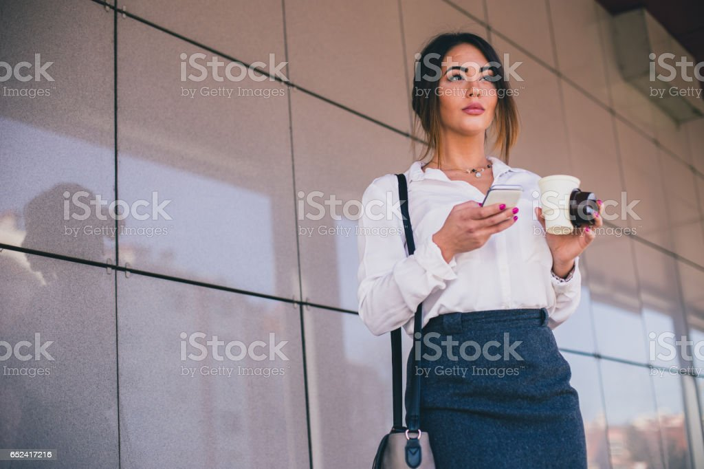 Beautiful businesswoman on a coffee break sending messages on her mobile phone stock photo