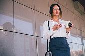 彼女の携帯電話にメッセージを送信するコーヒー ブレークに美しい実業家