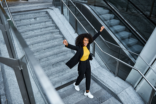 Portrait of  female business executive standing on office escalator