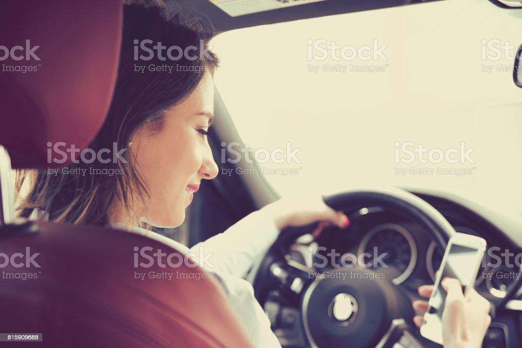 Hermosa empresaria enviar un texto mientras se conduce para trabajar - foto de stock