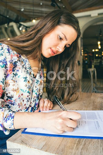 istock Beautiful Businesswoman Signing Contract In A Cafe Indoors 481433250