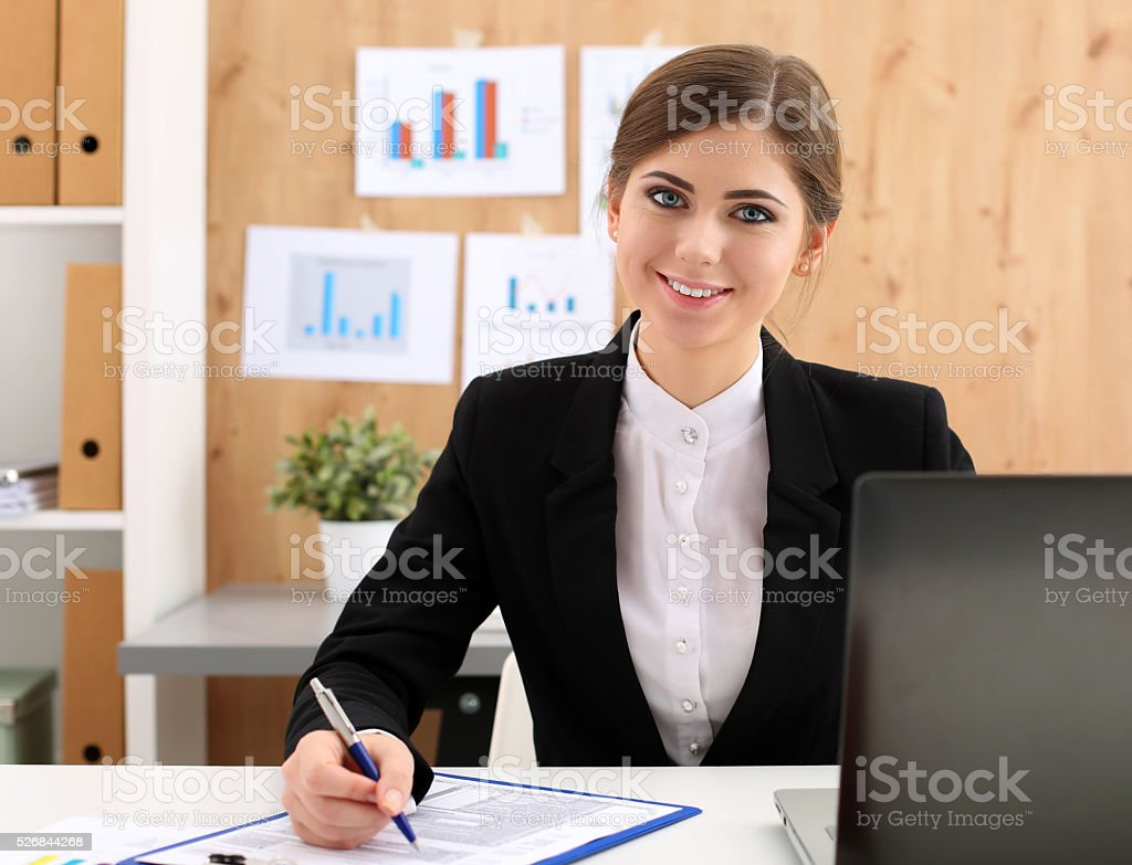 Beautiful businesswoman sit at workplace in office work with pap stock photo