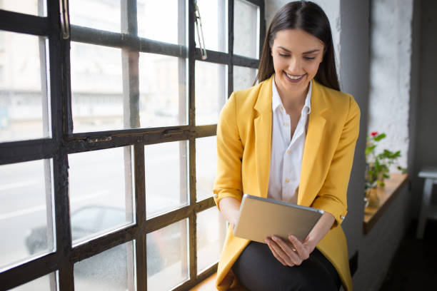 Beautiful businesswoman sitting and working on digital tablet stock photo