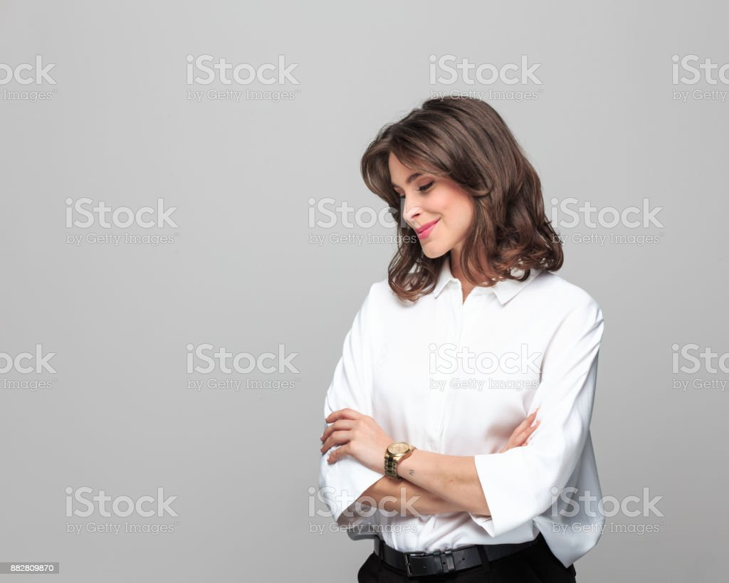 Beautiful businesswoman smiling with her eyes closed Beautiful businesswoman smiling with her arms crossed and eyes closed while standing over grey background. Female entrepreneur in studio. 25-29 Years Stock Photo