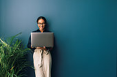istock Beautiful businesswoman standing at home and holding laptop computer oh hands 1223487232