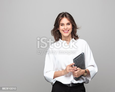 istock Beautiful businesswoman standing with a diary 882810010