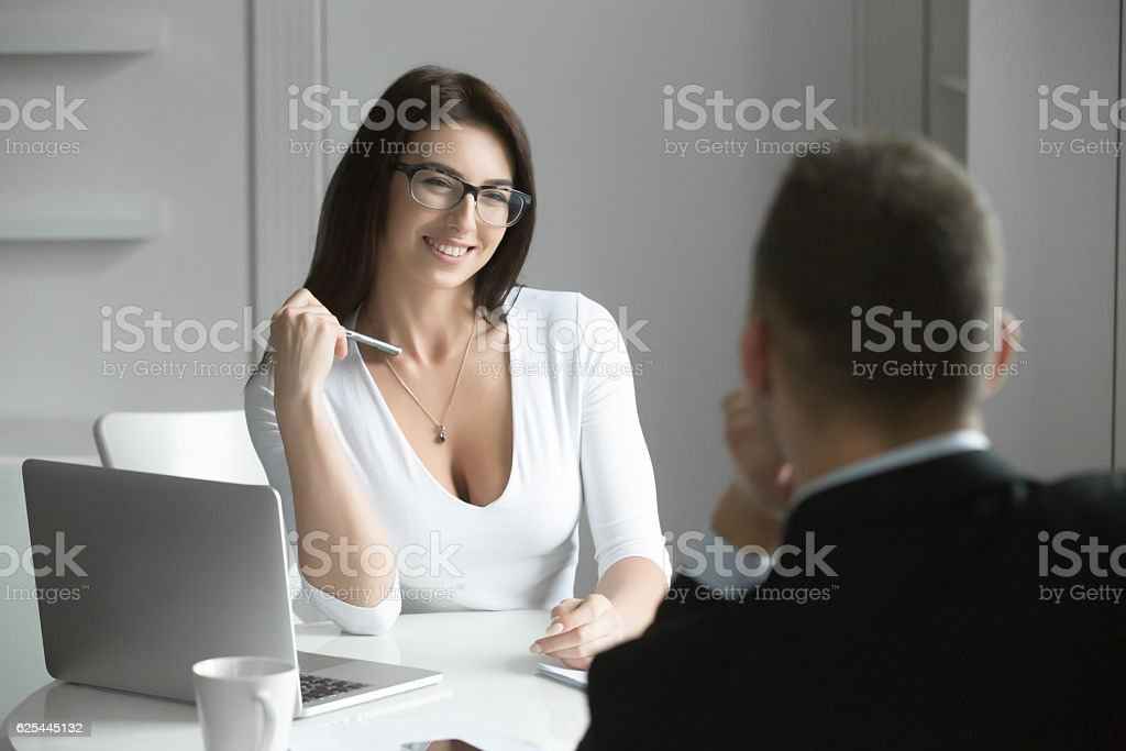 Beautiful businesswoman talking to a male job applicant stock photo