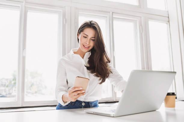 Schöne Geschäftsfrau mit Laptop und Smartphone – Foto