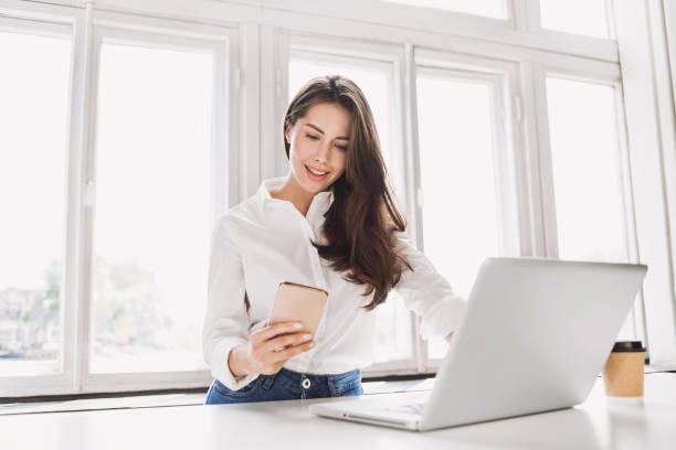 Beautiful businesswoman using laptop and smart phone stock photo
