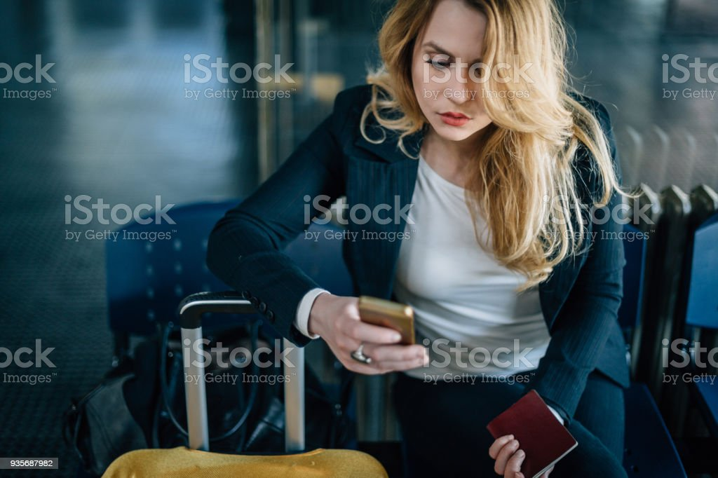Beautiful businesswoman using phone at the airport and holding passport stock photo