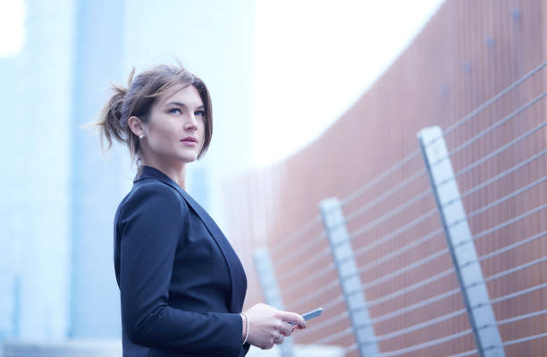 beautiful businesswoman walking with mobile phone stock photo