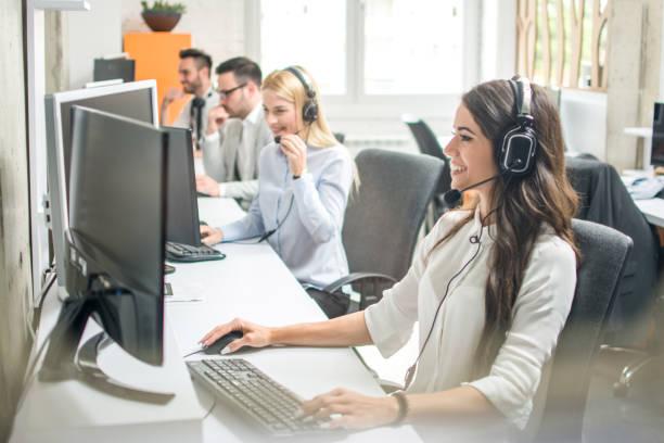 Schöne Geschäftsfrau mit Headset im Gespräch mit einem Kunden im Kundenservice-Center. – Foto
