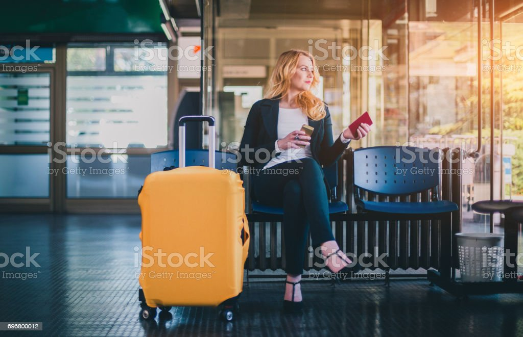 Beautiful businesswoman with suitcase sitting in airport waiting room with passport and using phone stock photo