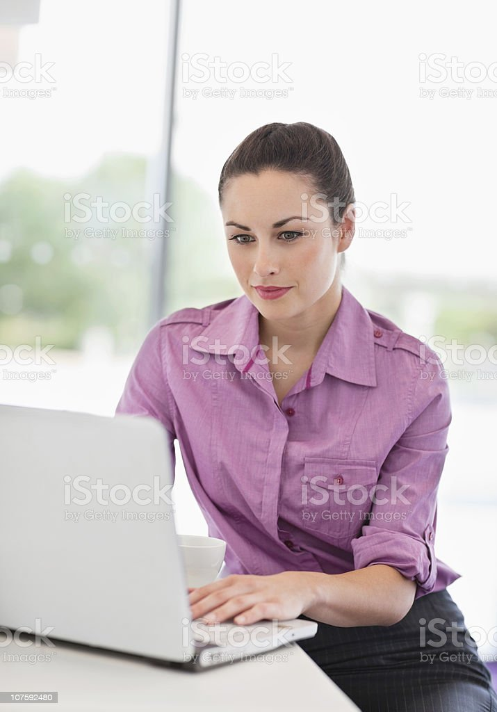 Beautiful businesswoman working on laptop in office cafeteria royalty-free stock photo