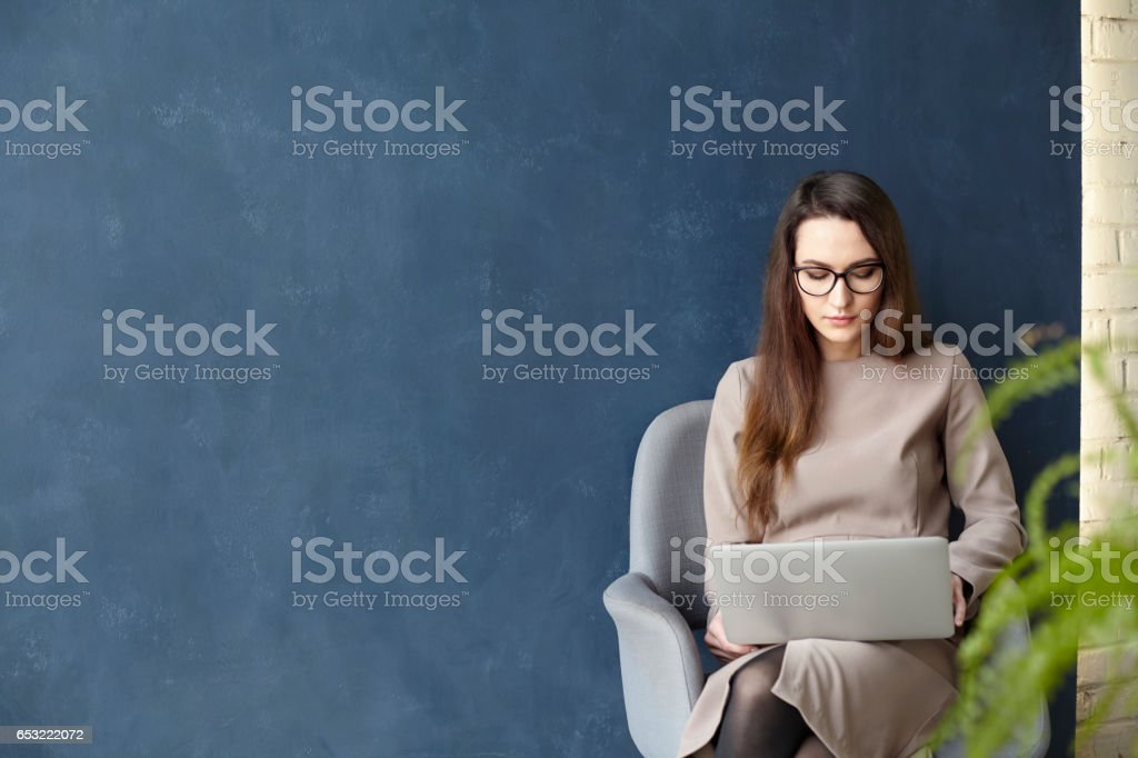 Beautiful businesswoman working on laptop while sitting in modern loft office. Dark blue wall background, day light stock photo