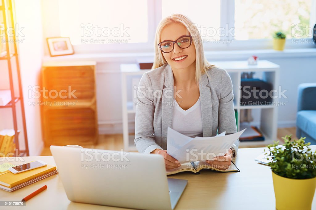 Beautiful businesswoman working with laptop and documents at hom stock photo