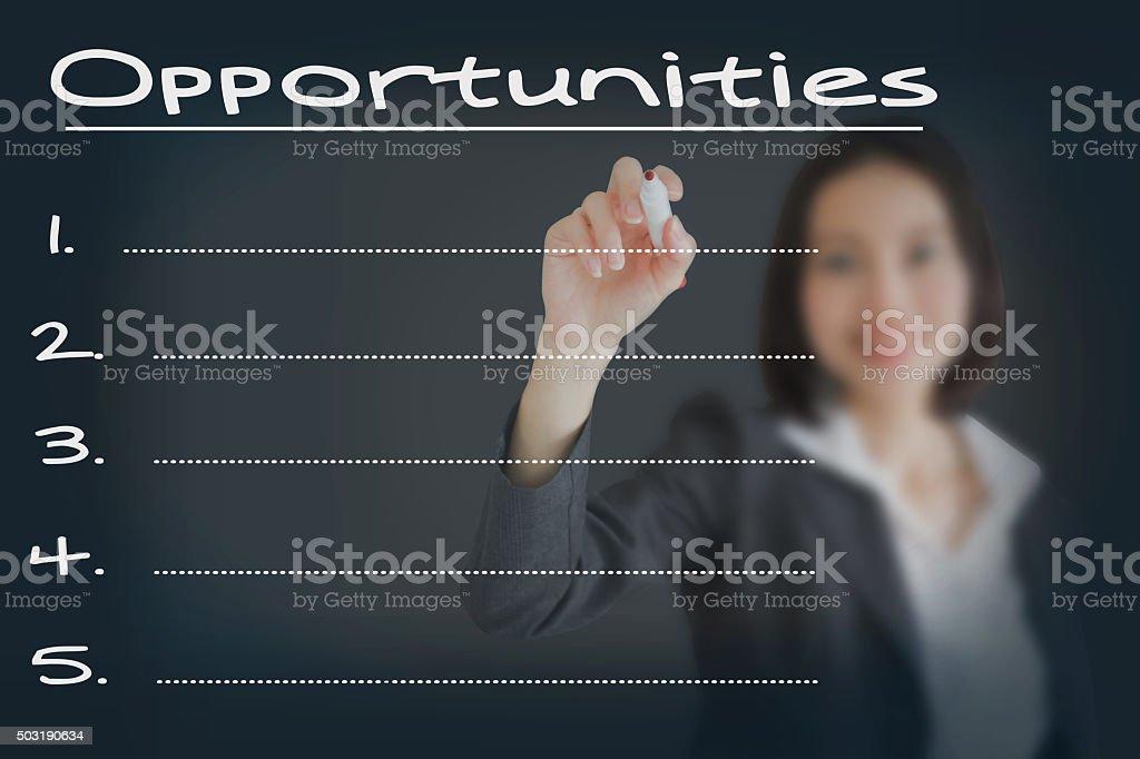 Beautiful businesswoman writing list of business weakness...