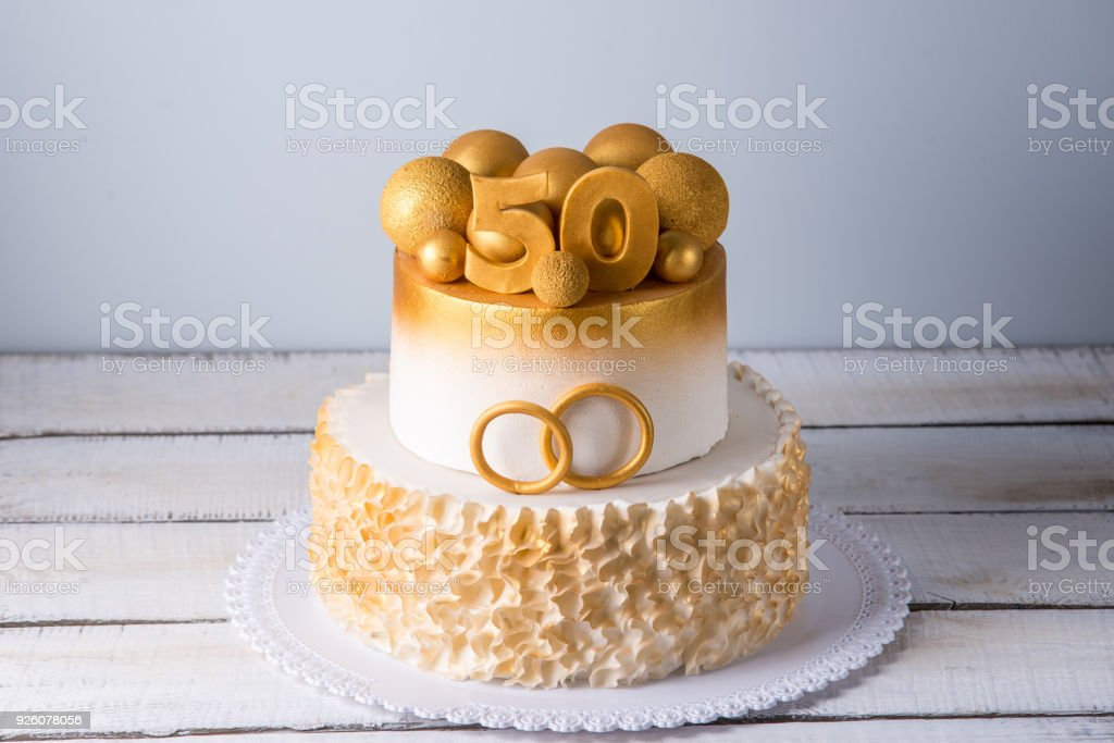 Beautiful cake for the 50th anniversary of the wedding decorated with gold balls and rings. Concept of festive desserts stock photo