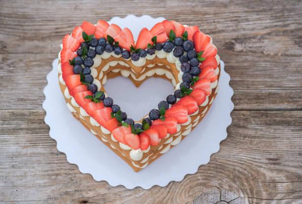 schöne kuchen in der form eines herzens auf einem hölzernen hintergrund. ansicht von oben. valentinstag, hochzeitstorte - hausgemachte hochzeitstorten stock-fotos und bilder