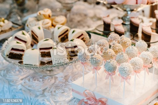 992836992 istock photo Beautiful cake pops. Colorful table with sweets and goodies for the wedding party reception, decorated dessert table. Delicious sweets on candy buffet. Dessert table for a party. cakes, cupcakes. 1132126378