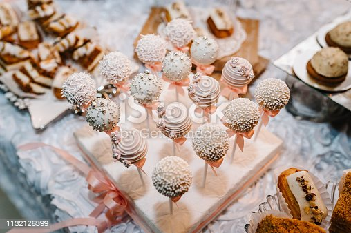 992836992 istock photo Beautiful cake pops. Colorful table with sweets and goodies for the wedding party reception, decorated dessert table. Delicious sweets on candy buffet. Dessert table for a party. cakes, cupcakes. 1132126399