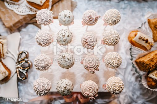 992836992 istock photo Beautiful cake pops. Colorful table with sweets and goodies for the wedding party reception. Delicious sweets on candy buffet. Dessert table for a party. cakes, cupcakes. flat lay. top view. 1132126403