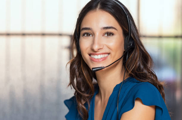 Beautiful call center consultant Customer support woman smiling and looking at camera. Portrait of happy customer support phone operator at call center wearing headset. Cheerful executive at your service working at office. call centre photos stock pictures, royalty-free photos & images