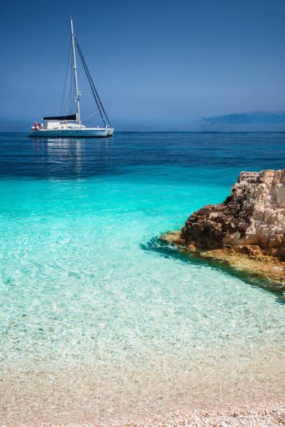 vackra lugna azurblå lagunen med segling katamaran yacht båt ankar. ren vit stenstrand med klippor i havet - katamaran bildbanksfoton och bilder