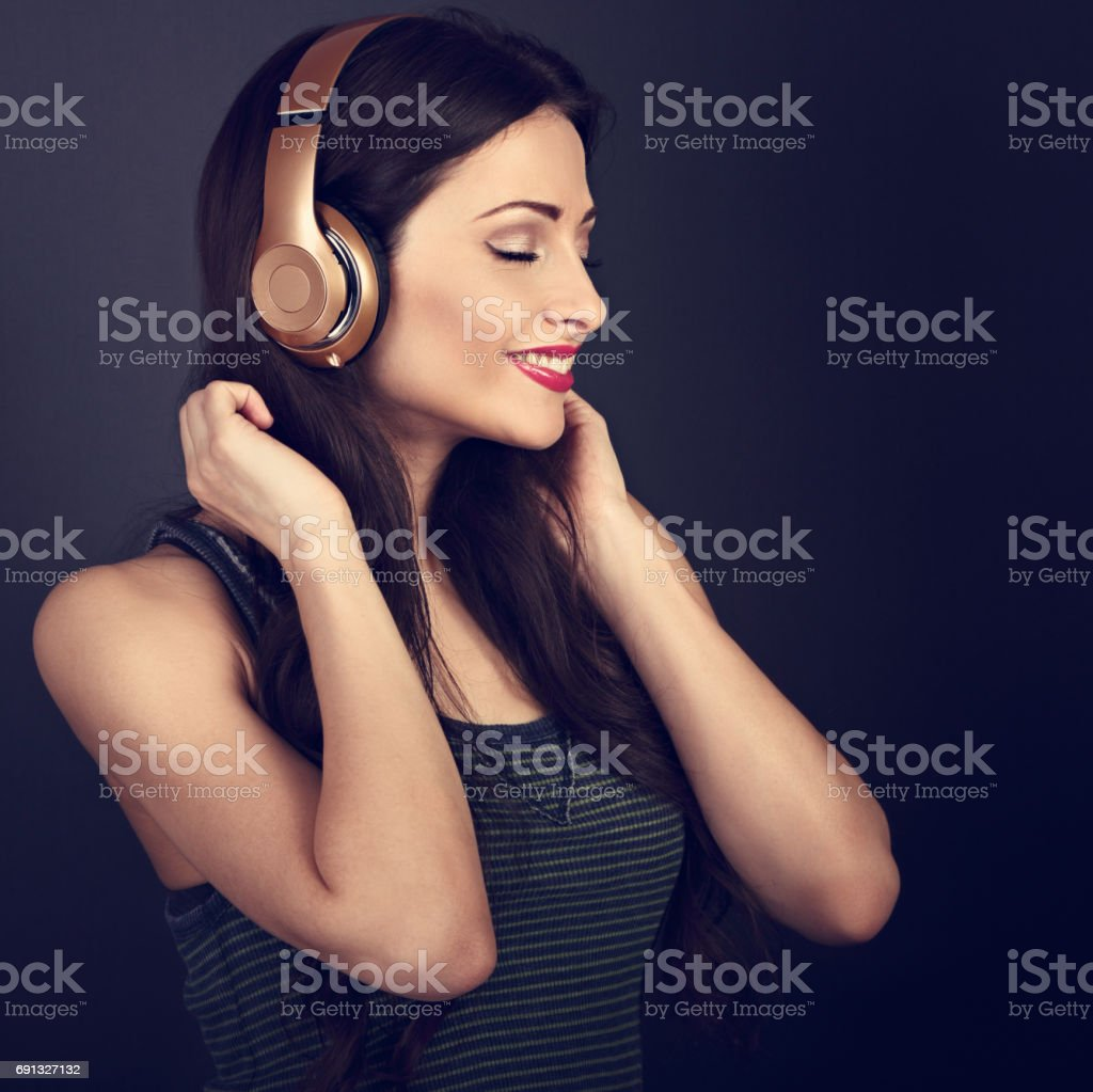 Beautiful calm young woman listening the music in wireless headphone with closed eyes on dark grey background. Closeup toned portrait stock photo