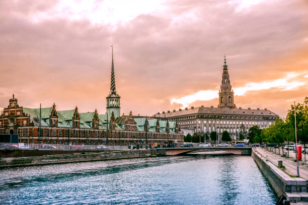 beautiful canal in copenhagen and view of stock exchange building at sunset - denmark stock photos and pictures