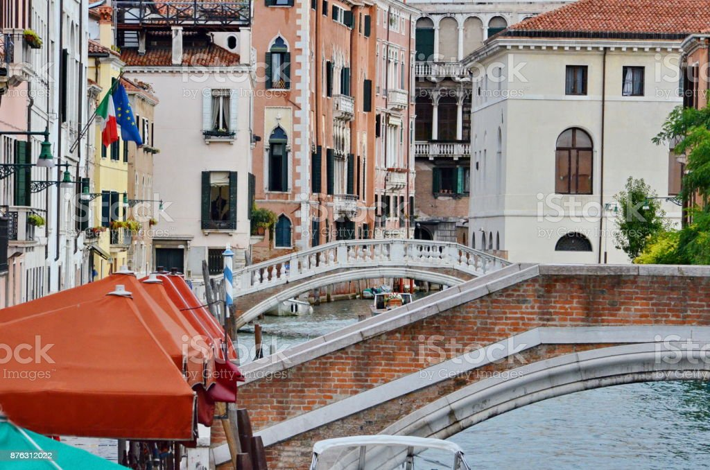 Beautiful canal with colorful buildings and footbridges in Venice, Italy stock photo