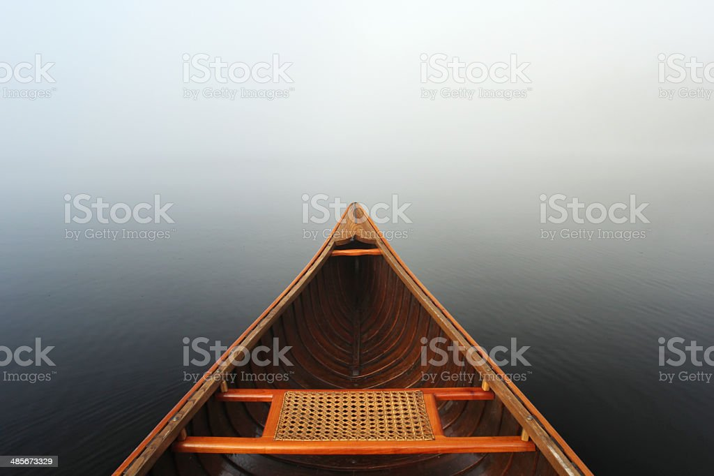 Beautiful canoe in mist and smooth waters stock photo