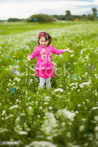 507271044istockphoto beautiful carefree girl playing outdoors in field 470698382
