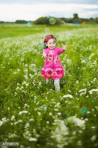 507271044istockphoto beautiful carefree girl playing outdoors in field 472165170
