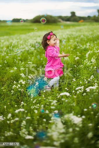 istock beautiful carefree girl playing outdoors in field 472165172