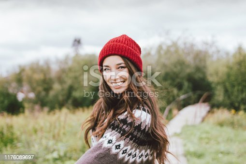 Beautiful carefree long hair asian girl in the red hat and knitted nordic sweater in autumn
