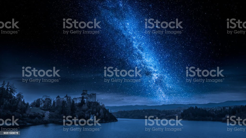 Beautiful castle by the lake at night with milky way stock photo