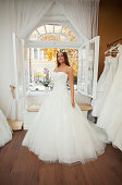 This is image of beautiful, elegant caucasian bride wearing wedding dress and wreath on her head. She is in bridal shop, selected wedding dresses are on right part of image. She is standing in front of window. Selective focus.