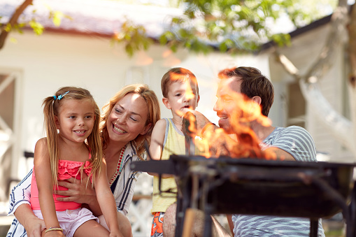 beautiful caucasian family of four making fire for barbeque