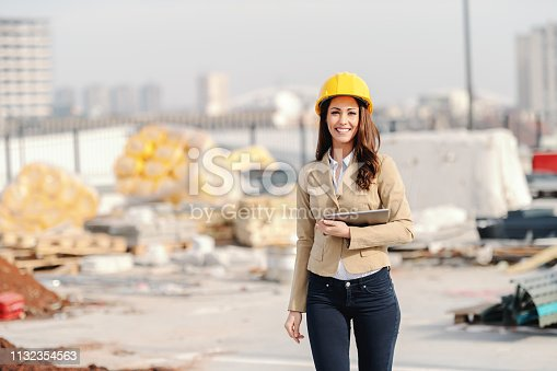 1129095769 istock photo Beautiful Caucasian female architect with long brown hair, toothy smile and helmet on head holding tablet while walking at construction site. 1132354563