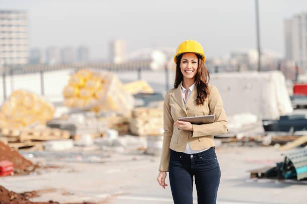 hermosa mujer caucásica arquitecto con cabello castaño largo, sonrisa toothy y casco en la cabeza sosteniendo tableta mientras camina en la obra. - arquitecta fotografías e imágenes de stock