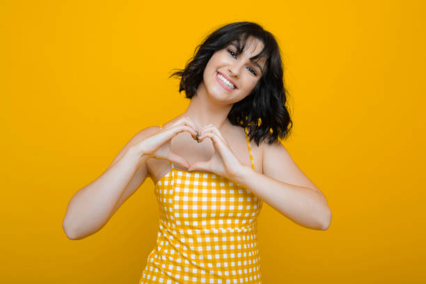 Beautiful caucasian female with short dark hair dressed in yellow dress looking at camera showing love with hands and laughing against a yellow studio wall. stock photo