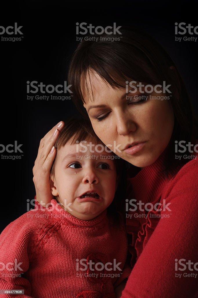 Beautiful Caucasian mama with a sad crying daughter stock photo