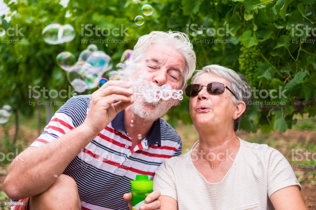 beautiful caucasian mature couple man and woman do soap bubbles together to play and have fun with joy, outdoor nature location for happy leisure activity for retired people with lifestyle stock photo