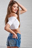 Beautiful Caucasian model in denim shorts and white crop top playfully posing with hand in back pocket and other touching her hair in white photo studio. Blurred brick wall background.