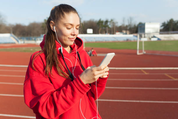 beautiful caucasian sporty woman to fashionable red hoodie listens to music in headphones through smartphone - ragazza auricolari rossi foto e immagini stock